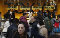 Una mujer mira el escaparate de una tienda de departamentos mientras gente camina por el paseo un paseo comercia del distrito de Ginza en Japón.  15 de febrero de 2015. La economía de Japón pasó de una recesión a un crecimiento en tasa interanual de un 2,2 por ciento en el último trimestre del año pasado, dándole un empuje a los esfuerzos del primer ministro Shinzo Abe para sacudir al país de décadas de estancamiento pese a perspectivas mundiales deterioradas. REUTERS/Yuya Shino