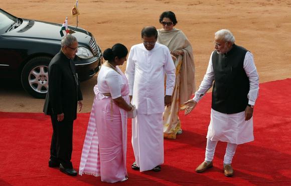 Indian Prime Minister Narendra Modi (R) gestures to Sri Lanka's President Mithripala Sirisena's wife Jayanthi Sirisena (2nd L) as India's President Pranab Mukherjee (L) looks on during Sirisena's ceremonial reception at the forecourt of India's Rashtrapati Bhavan presidential palace in New Delhi February 16, 2015. REUTERS/Adnan Abidi