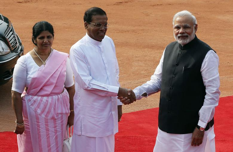 Sri Lanka's President Mithripala Sirisena (C) shakes hands with Indian Prime Minister Narendra Modi (R) as his wife Jayanthi Sirisena looks on during Sirisena's ceremonial reception at the forecourt of India's Rashtrapati Bhavan presidential palace in New Delhi February 16, 2015. REUTERS/Adnan Abidi