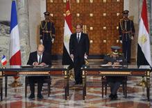 Le ministre français de la Défense Jean-Yves Le Drian et son homologue égyptien Sedki Sobhi lors d'une cérémonie de signature lundi au Caire, sous le regard du président égyptien Abdel Fattah al Sissi. Dassault Aviation a signé lundi dans la capitale égyptienne son premier contrat d'exportation de l'avion de combat Rafale. /Photo prise le 16 février 2015/REUTERS/Présidence égyptienne