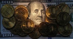 Долларовая купюра и рублевые монеты в Санкт-Петербурге 22 октября 2014 года. Рубль значительно вырос вечером среды за счет продаж экспортной выручки под предстоящие налоги в условиях тонкого рынка и в надежде на сохранение перемирия на востоке Украины, игнорируя текущее падение нефтяных цен. REUTERS/Alexander Demianchuk