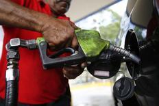 Una persona carga combustible a su automóvil en una estación gasolinera en Caracas. Imagen de archivo, 7 agosto, 2014.  La cesta de crudo venezolana ganó 3,51 dólares por barril (dpb) en la semana, ante la escalada de violencia en Libia y la tensión en Ucrania, además de una disminución en el número de plataformas petroleras activas en Estados Unidos, dijo el viernes el Ministerio de Petróleo. REUTERS/Jorge Silva