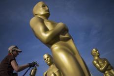 Una persona pinta estatuas del Oscar cerca del Teatro Dolby en Hollywood, 18 febrero, 2015. Puede que para el observador externo Hollywood irradie glamour natural, pero cualquiera que haga películas dirá que es un proceso largo y arduo, que conlleva además continuos golpes al ego y las cuentas bancarias. REUTERS/Adrees Latif