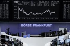 Traders are pictured at their desks in front of the DAX board at the Frankfurt stock exchange February 23, 2015. REUTERS/Staff/remote