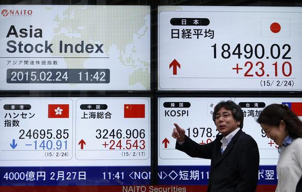 Pedestrians walk past an electronic board showing the stock market indices of various Asian countries outside a brokerage in Tokyo February 24, 2015.  REUTERS-Yuya Shino