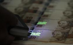Funcionário verifica folhas de papel-moeda durante visita da mídia à Casa da Moeda, no Rio de Janeiro. 23/08/2012 REUTERS/Sergio Moraes