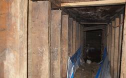 A 33-foot-long tunnel supported using lumber found in Toronto, Ontario is pictured in this handout photo provided by Toronto Police, February 24, 2015. Police in Toronto have discovered a tunnel with electricity supplied by a generator near one of the venues for this summer's Pan American Games, a spokesman said on Monday. REUTERS/Toronto Police/Handout