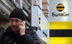 A man speaks on the phone near an office of Beeline, the brand owned by mobile phone operator Vimpelcom, in Moscow, November 12, 2014. Mobile operator Vimpelcom said it expected its Russian operations to improve in the last three months of the year, after revenues there showed signs of recovery in the third quarter and the group added subscribers. REUTERS/Maxim Shemetov (RUSSIA - Tags: BUSINESS TELECOMS)