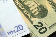 Банкноты по 20 долларов и евро. Париж, 28 октября 2014 года. Доллар растет к евро в четверг после того, как глава ФРБ Сент-Луиса Джеймс Буллард сказал, что сильный доллар имеет лишь незначительное влияние на монетарную политику и экономику США, а также благодаря статистике. REUTERS/Philippe Wojazer
