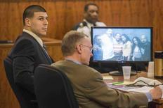Aaron Hernandez (L) sits beside his attorney Charles Rankin as a group photo including him is shown during his murder trial at the Bristol County Superior Court in Fall River, Massachusetts, February 25, 2015.  REUTERS/Aram Boghosian/Pool