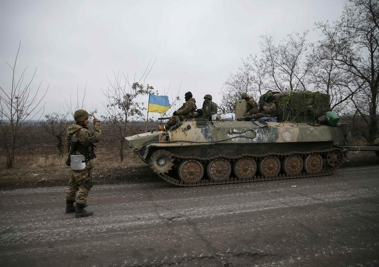 A convoy of Ukrainian armed forces including armoured personnel carriers, military vehicles and cannons prepare to move as they pull back from the Debaltseve region, in Paraskoviyvka, eastern Ukraine, February 26, 2015. REUTERS/Gleb Garanich