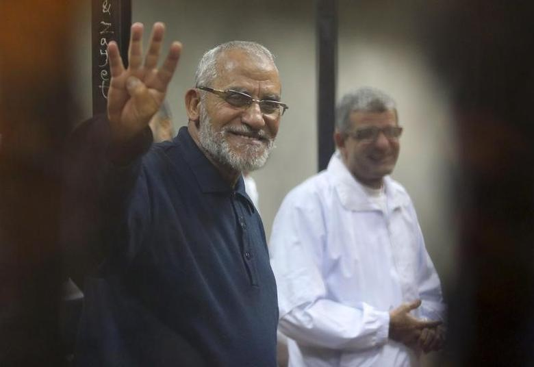 Muslim Brotherhood's Supreme Guide Mohamed Badie (L) flashes the Rabaa sign as he stands behind bars during his trial with ousted Egyptian President Mohamed Mursi and other leaders of the brotherhood at a court in the police academy on the outskirts of Cairo December 14, 2014.   REUTERS/Asmaa Waguih