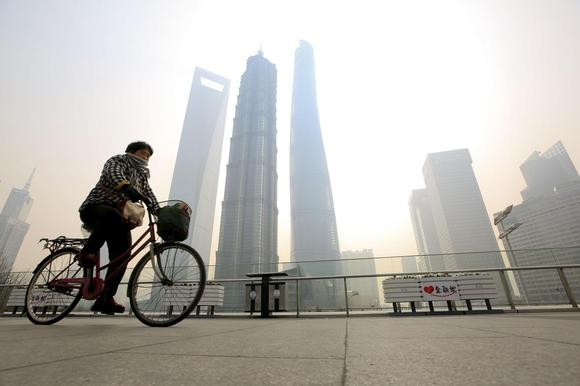 A woman covers her nose and mouth with her scarf amid heavy haze, as she rides a bicycle at the Pudong financial area in Shanghai, February 12, 2015.  REUTERS/Aly Song