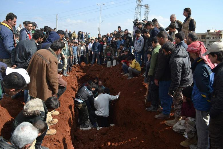 People bury the bodies of eight Hazzm brigade fighters, who were killed during clashes with al Qaeda's official Syria wing Nusra Front fighters in Reef al-Mohandeseen al-Thani and the Mashtal area, in Al-atarib Aleppo countryside February 28, 2015.  REUTERS/Abdalghne Karoof