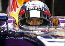 Red Bull Formula One driver Sebastian Vettel of Germany sits in the car at the pit lane during the third practice session of the Abu Dhabi F1 Grand Prix at the Yas Marina circuit in Abu Dhabi November 22, 2014. REUTERS/Ahmed Jadallah