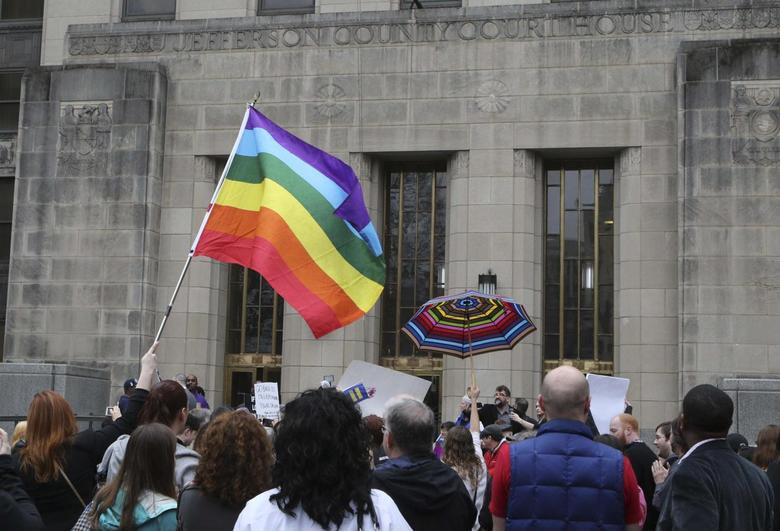 Supporters of same-sex marriage hold a rainbow flag and a rainbow umbrella outside Jefferson County Courthouse in Birmingham, Alabama February 9, 2015. REUTERS/Marvin Gentry