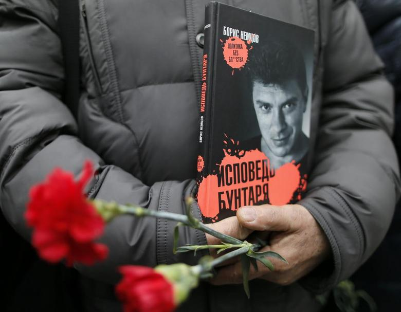 A visitor holds flowers and a book ''Confessions of the Rebel'' by Russian leading opposition figure Boris Nemtsov while waiting to attend a memorial service before the funeral of Nemtsov in Moscow, March 3, 2015. REUTERS/Maxim Shemetov
