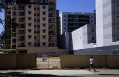 A man walks past a vacant block next to apartment buildings in the Western Australian capital city of Perth March 5, 2015. REUTERS/David Gray