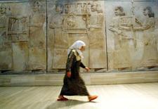 Iraquiana passa por mural assírio em museu de Bagdá retirado da cidade de Nimrud, em foto de arquivo. 03/07/2003 REUTERS/Radu Sigheti