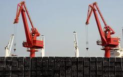 Las exportaciones de China crecieron un 48,3 por ciento en febrero respecto al año anterior, mientras las importaciones cayeron un 20,5 por ciento, generando un superávit comercial de 60.600 millones de dólares para el mes, informó el domingo la Administración General de Aduanas. En la imagen, tubos de acero destinados a la exportación delante de grúas en un puerto de Lianyungang, en la provincia de Jiangsú, 7 de marzo de 2015.  REUTERS/Stringer