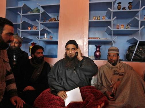 Masarat Alam Bhat (2nd R), a Kashmiri separatist leader, speaks on his mobile phone at his residence in Srinagar March 9, 2015. REUTERS-Danish Ismail