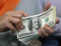 Mulher conta notas de dólar em casa de câmbio em Jacarta. 13/06/2012 REUTERS/Beawiharta