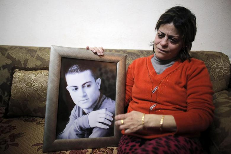 The mother of Muhammad Musallam, an Israeli Arab held by Islamic State in Syria as an alleged spy, weeps as she holds his photograph in her East Jerusalem home February 12, 2015.  REUTERS/Ammar Awad