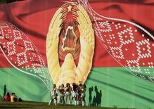 Женщины танцуют у плаката, на котором изображены флаг и герб Белоруссии в Минске 3 июля 2014 года.  США в ответ на участие президента Белоруссии Александра Лукашенко в качестве посредника в урегулировании конфликта на Украине отменили санкции, введенные четыре года назад против белорусской государственной компании Белоруснефть. REUTERS/Vasily Fedosenko