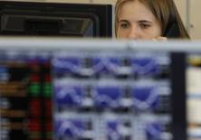 Трейдер в торговом зале инвестбанка Ренессанс Капитал в Москве 9 августа 2011 года. Рублевые цены российских акций отскочили в среду после заметного падения предыдущей сессии, но не поддержали общее восстановление акции Системы на фоне корпоративных новостей и бумаги Мегафона, сообщившего о сокращении прибыли в 2014 году из-за рубля. REUTERS/Denis Sinyakov