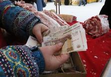 Женщина держит в руках рублевые купюры на рынке в Красноярске 14 января 2015 года. Рубль показывает разнонаправленную динамику к доллару и евро на дневных торгах среды, отражая укрепление валюты США и падение единой европейской на мировых рынках, подешевевшую нефть, а также переплетение внутренних денежных потоков, как реальных, так и спекулятивных. REUTERS/Ilya Naymushin