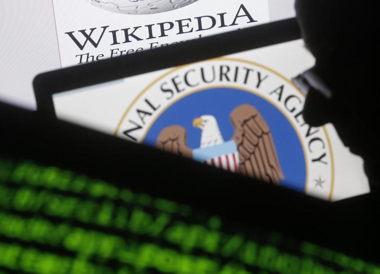 A man is seen near cyber code and the U.S. National Security Agency logo in this photo illustration taken in Sarajevo March 11, 2015. REUTERS/Dado Ruvic