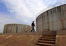 Рабочий компании Canadian Pacific Rubiales Petroleum Company проходит мимо нефтехранилищ на месторождении Кампо Рубиалес в Колумбии. 11 февраля 2015 года. Цены на нефть растут, так как спекулянты покрывают позиции накануне истечения апрельских контрактов. REUTERS/Jose Miguel Gomez