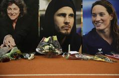 The portraits of (LtoR) French yachtswoman Florence Arthaud, Olympic boxer Alexis Vastine and Olympic swimmer Camille Muffat are seen during a tribute ceremony at the training headquarters of INSEP (National Institute for Sport and Physical Education) in Paris, March 11, 2015. REUTERS/Christian Hartmann