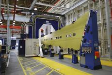 A blue, horseshoe-shaped wing assembly machine glides over a yellow wing panel, which will become part of a 737 jetliner, at the Boeing factory in Renton, Washington, in this picture taken March 12, 2015. REUTERS/Tim Hepher