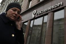 Женщина у салона Ростелекома в Москве. 21 ноября 2012 года. Подконтрольный государству Ростелеком в четвертом квартале 2014 года получил 2 миллиарда рублей убытка от основного - фиксированного - бизнеса по сравнению с 2,7 миллиарда прибыли годом ранее, сообщила компания в понедельник. REUTERS/Maxim Shemetov
