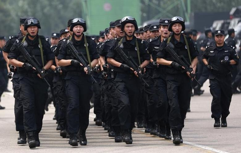 Policemen of a Special Weapons and Tactics (SWAT) team shout slogans as they gather for a anti-terrorism drill in Shenyang, Liaoning province June 16, 2014. REUTERS/Stringer