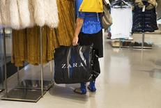 A woman holds a bag inside a Zara store in Madrid September 12, 2014. REUTERS/Andrea Comas
