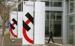 A man walks past the logos of Swiss cement maker Holcim in front of the company's headquarters in Zurich February 23, 2015.  REUTERS/Arnd Wiegmann
