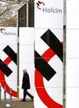 Un hombre pasa junto a las oficinas de Holcim en Zúrich, feb 23 2015. Las cementeras Holcim y Lafarge, que buscan salvar su acuerdo de fusión, están discutiendo el nuevo liderazgo del grupo combinado que podría dejar al jefe de Lafarge, Bruno Lafont, en un papel menor, dijeron el miércoles fuentes familiares con el tema.  REUTERS/Arnd Wiegmann