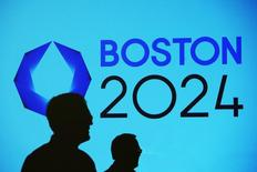 People cast shadows on a video display before a news conference explaining Boston's bid to host the 2024 Summer Olympics in Boston, Massachusetts January 21, 2015. REUTERS/Brian Snyder