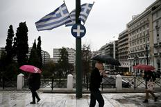 People holding umbrellas make their way next to fluttering Greek national flags on the main Constitution (Syntagma) square during heavy rainfall in Athens March 13, 2015.  REUTERS/Alkis Konstantinidis