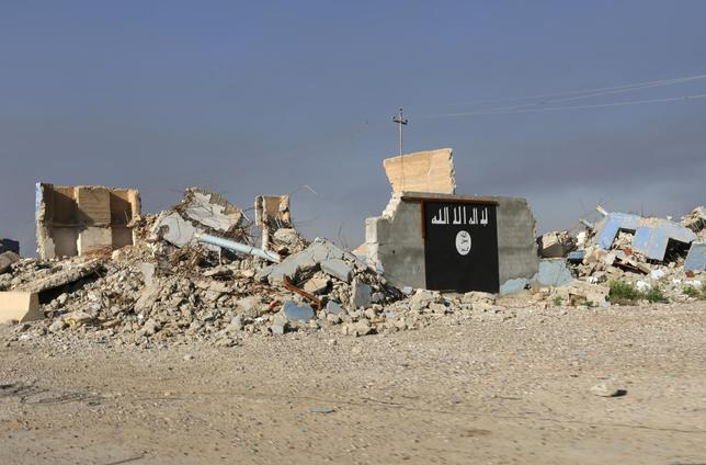 A destroyed building with a wall painted with the black flag commonly used by Islamic State militants, is seen in the town of al-Alam March 10, 2015. REUTERS/Thaier Al-Sudani