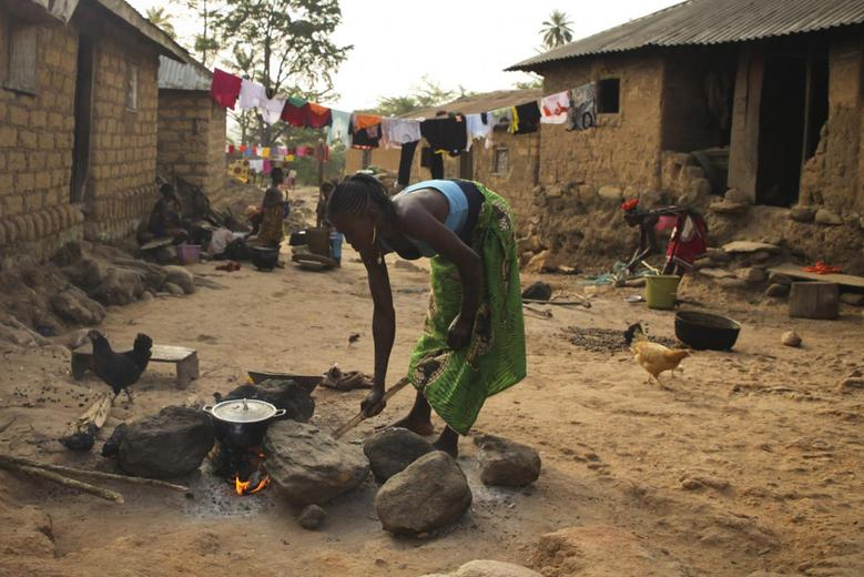A woman cooks in Meliandou February 4, 2015. REUTERS/Misha Hussain