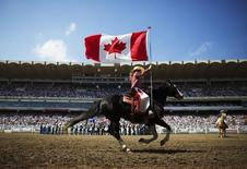 A Calgary Stampede rodeo girl carries the Canadian flag during the singing of the national anthem during day 2 of the Calgary Stampede rodeo in Calgary, Alberta, July 5, 2014. REUTERS/Todd Korol