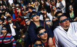 Pupils of the Deutschherren school and their teachers use protective glasses to watch a partial solar eclipse in Frankfurt, Germany, March 20, 2015.  REUTERS/Kai Pfaffenbach