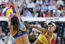 Foto de archivo de la china Xue Chen bloqueando un remate de la brasileña Juliana en el partido por el tercer puesto del voleibol de playa en los Juegos Olímpicos de Londres. Ago 8, 2012. El voleibol playa tendrá partidos a la medianoche en las playas de Copacabana durante los Juegos Olímpicos de Río de Janeiro 2016, con una atmósfera de celebración y fácil acceso a los bares cercanos, dijo a Reuters el director de la federación del deporte. REUTERS/Dominic Ebenbichler
