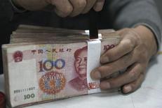 El nivel actual del yuan es apropiado porque refleja la oferta y demanda de divisas y los fundamentos económicos, dijo el sábado un alto funcionario del banco central chino, restándole importancia a los rumores de una presunta intervención oficial. En la imagen de archivo, un empleado bancario cuenta billetes en Huaibe en abril de 2011. REUTERS/Stringer/Files