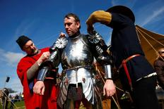 A reenactor is helped into his armour at the site of the Battle of Bosworth ahead of the arrival of Richard III's reburial procession, near Leicester, central England, March 22, 2015.  REUTERS/Eddie Keogh