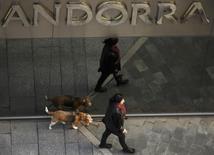A woman and her dog walk past a branch of Banca Privada D'Andorra (BPA) in Andorra la Vella, March 12, 2015.  REUTERS/Sergio Perez