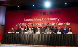 Canada's Finance Minister Joe Oliver (standing, C) looks on as representatives from Canadian banks sign agreements at an Industrial and Commercial Bank of China (ICBC) event that is launching a Renminbi (RMB) clearing centre and trading hub in Toronto, March 23, 2015.  REUTERS/Mark Blinch